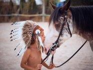 Bambino tranquillo con gli occhi chiusi che indossa il tradizionale legame del cofano di guerra indiano con lo stallone di cavallo su sfondo sfocato — Foto stock