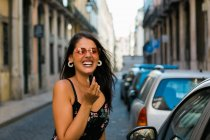 Woman in sunglasses and dress putting on lipstick while looking at camera, standing near car mirror on sunny street — Stock Photo