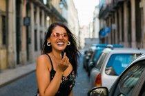 Mulher de óculos de sol e vestido colocando batom enquanto olha para a câmera, de pé perto do espelho do carro na rua ensolarada — Fotografia de Stock