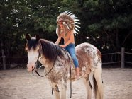 Serious boy in authentic Indian feather hat riding horse in park — Stock Photo