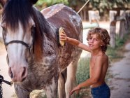 Content boy in jeans grooming horse with brush on ranch and looking at camera on blurred background — Stock Photo