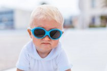 Portrait of a blonde baby with sunglasses on the beach — Stock Photo