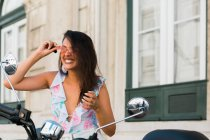 Beautiful funny woman in sunglasses looking at motorbike mirror on street — Stock Photo