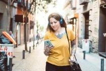 Mulher tatuada atenta em fones de ouvido usando smartphone enquanto estava na ensolarada rua da cidade — Fotografia de Stock