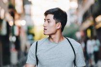 Content asian man in t shirt strolling along urban summer street — Stock Photo