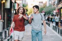 Uomini multietnici interessati spensierati in abiti casual con gesti longboard e parlare mentre passeggiano lungo la strada della città — Foto stock