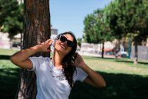 Мирная женщина в солнечных очках и наушниках слушает музыку, сидя на траве в парке — стоковое фото