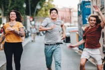 Smiling multiethnic competitive people in casual clothes hurrying and running along urban street — Stock Photo