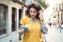 Femme tatouée attentive dans un casque en utilisant un smartphone tout en se tenant debout sur la rue ensoleillée de la ville — Photo de stock