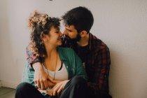 Freudig lässiges Paar lächelt und umarmt, während es auf dem Boden sitzt und sich zu Hause an weiße Wand lehnt — Stockfoto