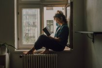 Side view of relaxed woman in casual outfit reading book while sitting barefoot on window sill in apartment — Stock Photo