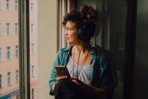 Густая кудрявая женщина в наушниках слушает музыку, просматривая смартфон и сидя на подоконнике в квартире, выглядывая из окна — стоковое фото