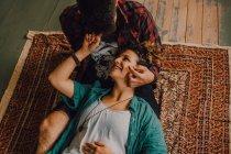 De dessus vue de couple décontracté joyeux souriant et étreignant tout en étant couché sur le sol à la maison — Photo de stock