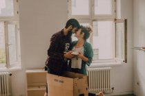 Hipster couple unpacking together boxes while standing barefoot in light room and cuddling — Stock Photo