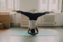 Visão traseira da mulher em activewear exercitando e fazendo headstand no chão no apartamento — Fotografia de Stock