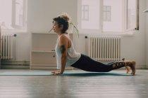 Вид сбоку гибкой женщины в верхней одежде, выполняющей упражнения и стоящей на руках на полу в квартире — стоковое фото