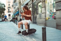 Homme occasionnel joyeux rire et parler sur smartphone tout en étant assis sur balustre sur la rue de la ville — Photo de stock
