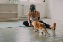 Забота о повседневной женщине, дающей пищу любопытной кошке, сидя босиком в минималистичной современной квартире — стоковое фото