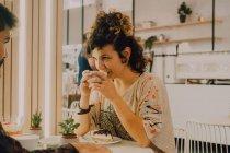 Seitenansicht einer glücklich lächelnden Frau, die im modernen Coffeeshop an einem Becher nippt — Stockfoto