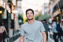 Contenuto asiatico uomo in t camicia passeggiando lungo urbano estate strada — Foto stock