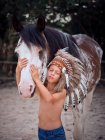 Tranquil child with closed eyes wearing traditional Indian war bonnet bonding with horse stallion on blurred background — Stock Photo