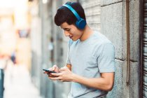 Joyful asian man in headphones using smartphone while standing on sunny city street. - foto de stock