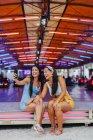 Содержание улыбающихся загорелых женщин, фотографирующих на смартфоне, сидя рядом с аттракционом развлечений на карнавале — стоковое фото