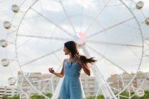 Злая спокойная женщина с длинными волосами в раздевалке, стоящая у входа на ярмарку в летний ветреный день — стоковое фото