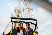 Enthousiaste femme insouciante et l'homme de s'amuser tout en appréciant la promenade à l'attraction colorée à funfair ensoleillé — Photo de stock
