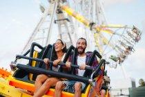Женщина и мужчина веселятся, наслаждаясь поездкой на солнечную ярмарку — стоковое фото