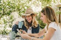 Случайные женщины делятся мобильным телефоном и пьют чай сидя за столом в зеленом саду — стоковое фото