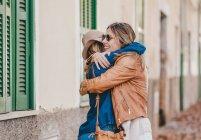 Веселі жінки зустрічаються і вітаються з обіймами на міській вулиці з листям. — стокове фото