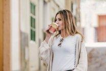 Стильная расслабленная женщина, идущая по улице и пьющая кофе в чашке — стоковое фото
