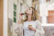 Mulher elegante relaxado andando rua abaixo e tomar café na xícara — Fotografia de Stock