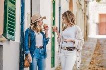 Mulheres elegantes e relaxadas conversando alegremente enquanto caminham pela rua tomando café em xícaras — Fotografia de Stock
