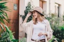Stilvolle entspannte Frau, die durch eine Stadt voller Pflanzen läuft — Stockfoto