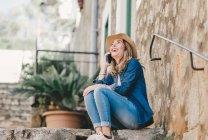 Vista lateral da jovem mulher sorrindo falando no telefone celular e sentado em escadas de pedra fora — Fotografia de Stock