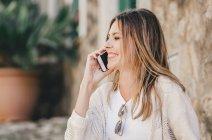 Femme souriante parlant sur téléphone portable et assis sur des escaliers en pierre à l'extérieur — Photo de stock