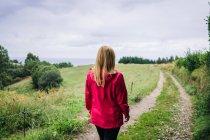 Mulher de pé no campo e olhando para longe — Fotografia de Stock