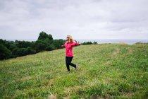 Femme joyeuse profitant du paysage rural et étirant les mains — Photo de stock