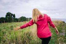 Mulher alegre desfrutando paisagem rural e estendendo as mãos — Fotografia de Stock