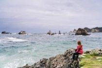 Femme assise sur le bord de mer vert pierreux — Photo de stock