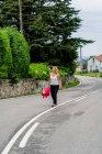 Donna gioiosa camminando su strada segnata e guardando via — Foto stock