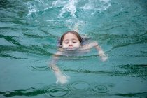 Little girl swimming in clean warm water of pond in spa and enjoying weather — Stock Photo