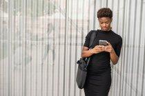 Mujer afroamericana con estilo enfocado en un teléfono inteligente de mensajería de vestido negro mientras está de pie sobre fondo metálico - foto de stock