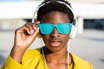 Афроамериканка в стильной яркой куртке и ярко-синих солнцезащитных очках в наушниках, стоящих рядом с современным зданием — стоковое фото