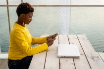 Mensajería femenina afroamericana concentrada con teléfono inteligente mientras se relaja en la mesa de madera - foto de stock