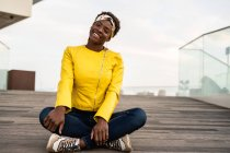 Elegante donna afroamericana in giacca moderna rilassante seduta sul pavimento in legno e guardando in macchina fotografica sorridente — Foto stock
