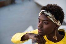 Alto angolo di donna afro-americana felice in elegante usura agghiacciante sulle scale appoggiate sul corrimano e guardando altrove — Foto stock