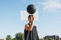 Молодой человек позирует с мячом на баскетбольной площадке на открытом воздухе . — стоковое фото